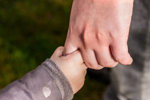 Barn och vuxen håller hand