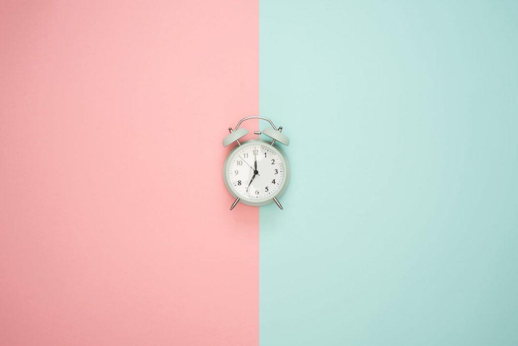 Rosa och ljusblå/ljusgrön bild med en klocka i mitten.